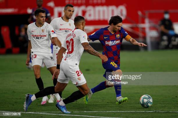 Lionel Messi of Barcelona is challenged by Diego Carlos of Sevilla during the Liga match between Sevilla FC and FC Barcelona at Estadio Ramon Sanchez...