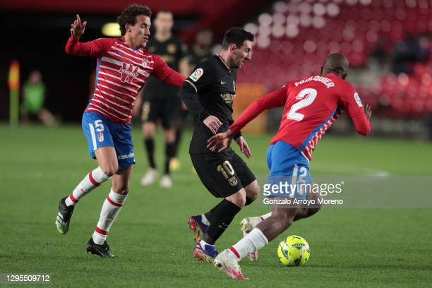 Lionel Messi of Barcelona is challenged by Dimitri Foulquier and Luis Milla of Granada during the La Liga Santander match between Granada CF and FC...