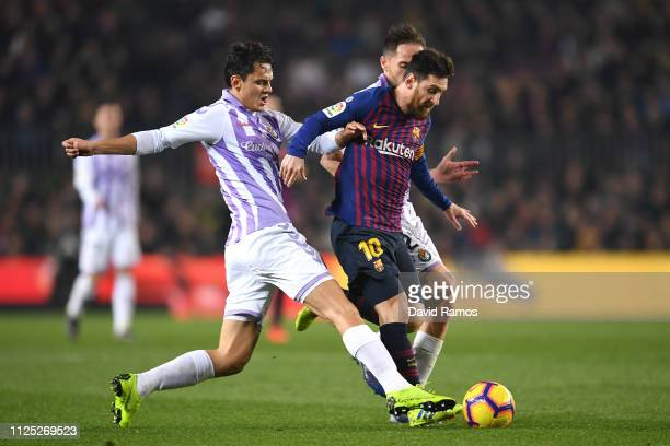 Lionel Messi of Barcelona is challenged by Enes Unal of Real Valladolid and Michel of Real Valladolid during the La Liga match between FC Barcelona...