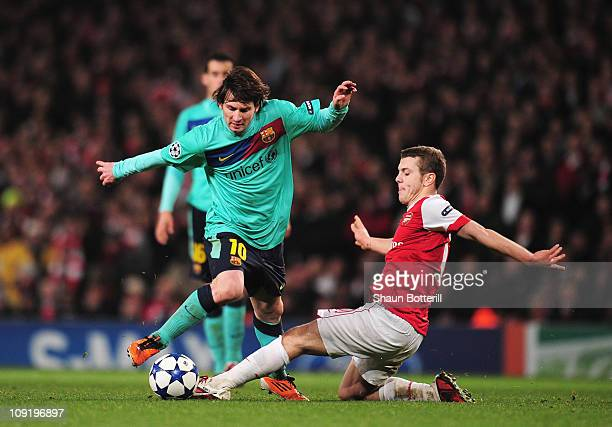Lionel Messi of Barcelona is challenged by Jack Wilshere of Arsenal during the UEFA Champions League round of 16 first leg match between Arsenal and...