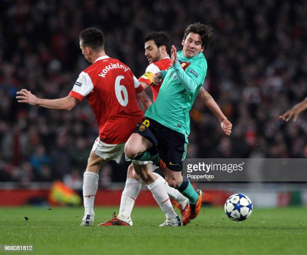 Lionel Messi of Barcelona is challenged by Laurent Koscielny and Cesc Fabregas of Arsenal during the UEFA Champions League round of 16 first leg...
