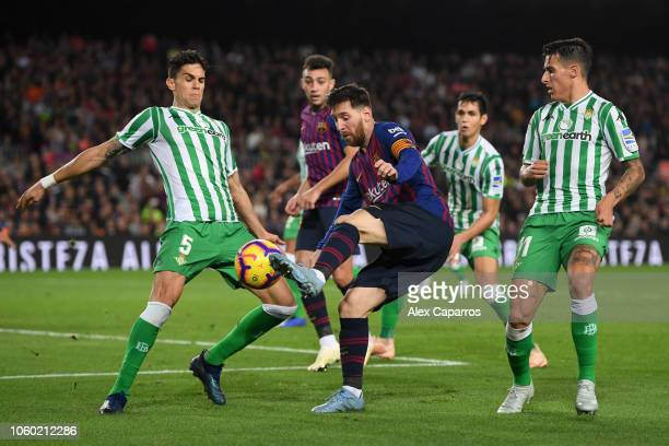 Lionel Messi of Barcelona is challenged by Marc Bartra of Real Betis and Cristian Tello of Real Betis during the La Liga match between FC Barcelona...