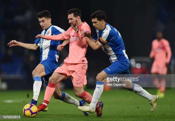 Lionel Messi of Barcelona is challenged by Marc Roca and Javi Lopez of RCD Espanyol during the La Liga match between RCD Espanyol and FC Barcelona at...
