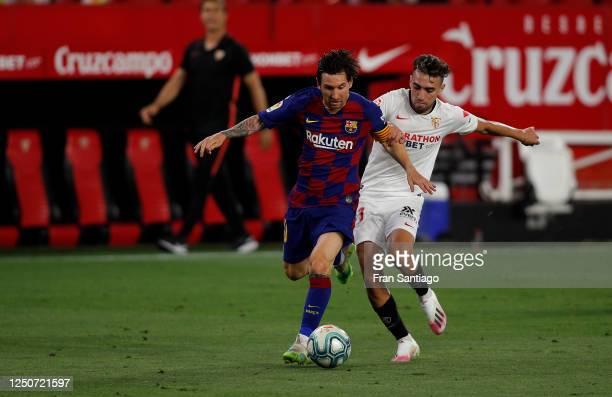 Lionel Messi of Barcelona is challenged by Munir El Haddadi of Sevilla during the Liga match between Sevilla FC and FC Barcelona at Estadio Ramon...
