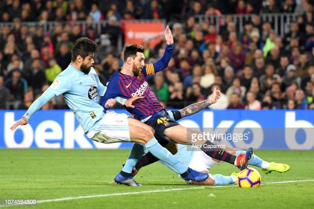 Lionel Messi of Barcelona is challenged by Nestor Araujo and Hugo Mallo of Celta Vigo during the La Liga match between FC Barcelona and RC Celta de...