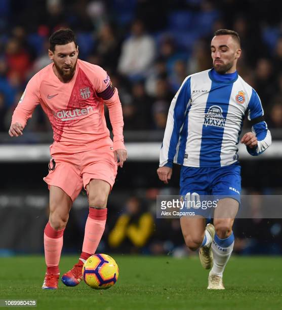 Lionel Messi of Barcelona is challenged by Sergi Darder Moll of RCD Espanyol during the La Liga match between RCD Espanyol and FC Barcelona at RCDE...