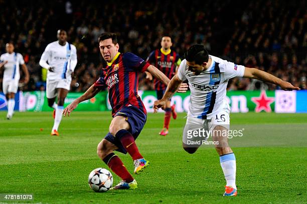 Lionel Messi of Barcelona is challenged by Sergio Aguero of Manchester City during the UEFA Champions League Round of 16, second leg match between FC...