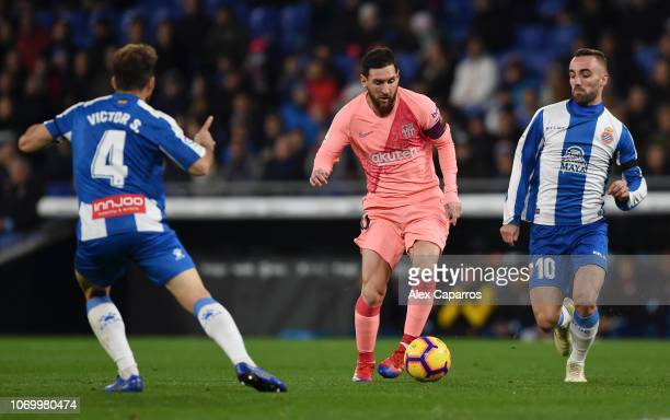 Lionel Messi of Barcelona is challenged by Victor Sanchez and Sergi Darder Moll of RCD Espanyol during the La Liga match between RCD Espanyol and FC...