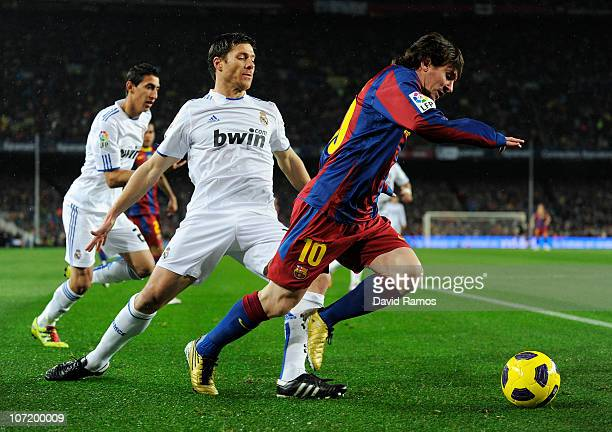 Lionel Messi of Barcelona is challenged by Xavi Alonso of Real Madrid during the La Liga match between Barcelona and Real Madrid at the Camp Nou...