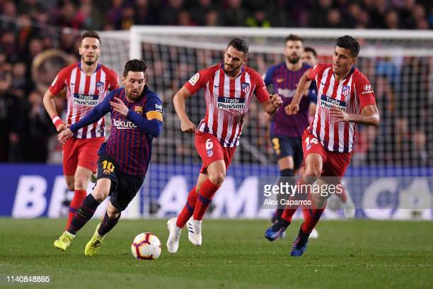 Lionel Messi of Barcelona is chased by Rodri and Koke of Atletico Madrid during the La Liga match between FC Barcelona and Club Atletico de Madrid at...