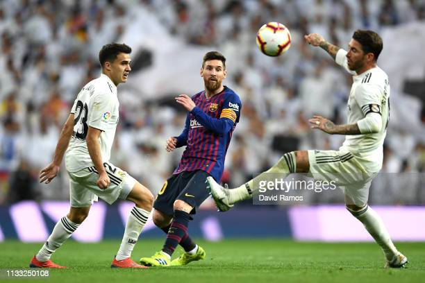 Lionel Messi of Barcelona is clowed down by Sergio Reguilon and Sergio Ramos of Real Madrid during the La Liga match between Real Madrid CF and FC...