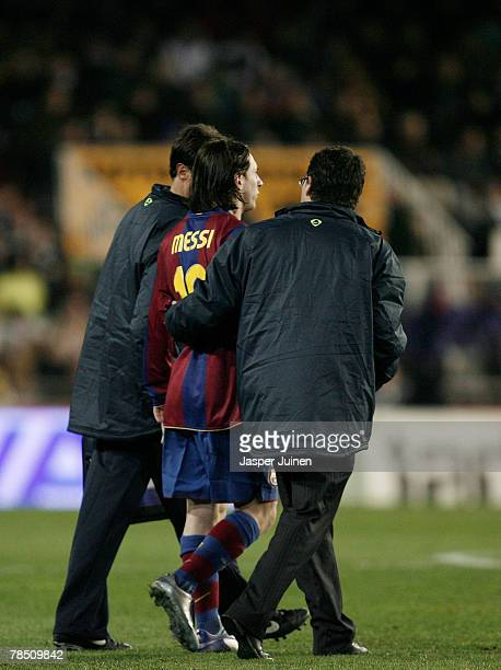 Lionel Messi of Barcelona is escorted off the pitch after injuring himself during the La Liga match between Valencia and Barcelona at the Mestalla...