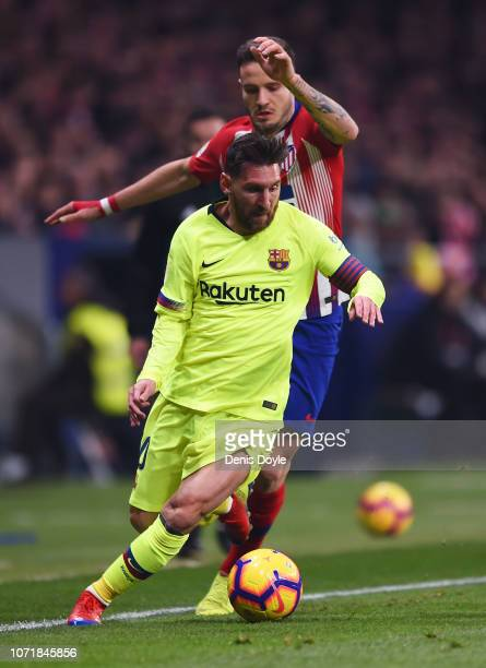 Lionel Messi of Barcelona is evades Saul Niguez of Atletico Madrid during the La Liga match between Club Atletico de Madrid and FC Barcelona at Wanda...