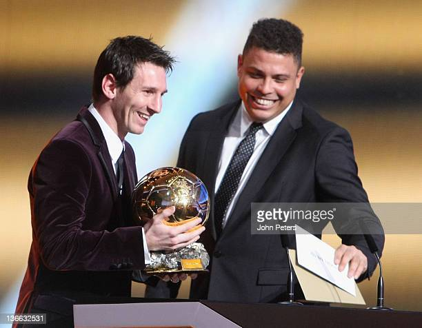 Lionel Messi of Barcelona is presented with the FIFA Ballon d'Or after winning it for the third year in succession by former footballer Ronaldo at...