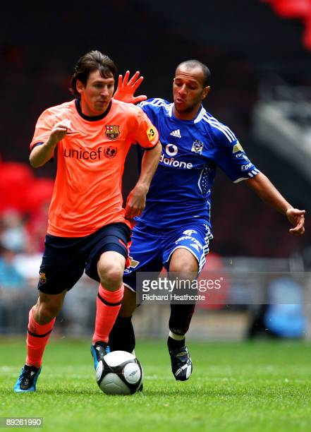 Lionel Messi of Barcelona is pursued by Moataz Eno of Al Ahly during the Wembley Cup match between Barcelona and Al Ahly at Wembley Stadium on July...