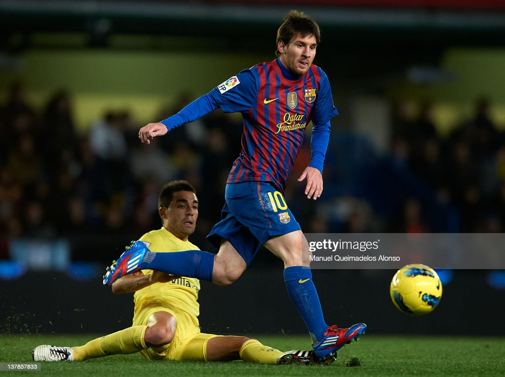 Lionel Messi (R) of Barcelona is tacked by Bruno Soriano of Villarreal during the la Liga match between Villarreal and Barcelona at El Madrigal on January 28, 2012 in Villarreal, Spain.