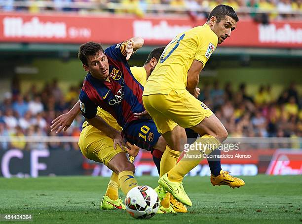 Lionel Messi of Barcelona is tackled by Cani and Mateo Pablo Musacchio during the La Liga match between Villarreal CF and FC Barcelona at El Madrigal...