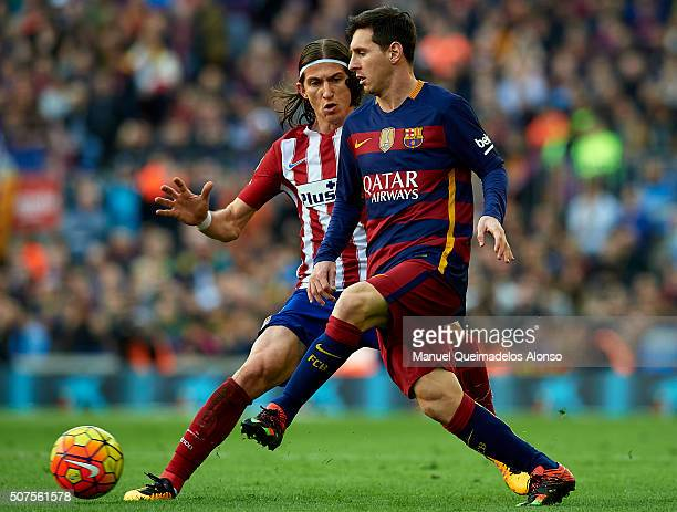Lionel Messi of Barcelona is tackled by Filipe Luis of Atletico de Madrid during the La Liga match between FC Barcelona and Atletico de Madrid at...