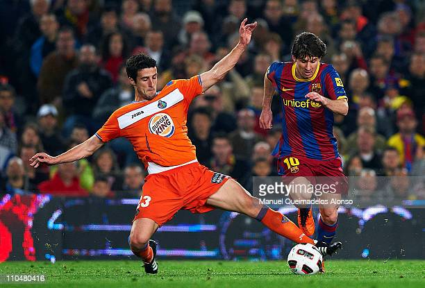Lionel Messi of Barcelona is tackled by Ivan Marcano of Getafe during the La Liga match between Barcelona and Getafe at Camp Nou on March 19 2011 in...