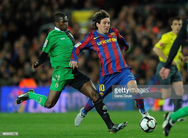 Lionel Messi of Barcelona is tackled by Pape Diop of Racing Santander during the La Liga match between Barcelona and Racing Santander at Camp Nou...