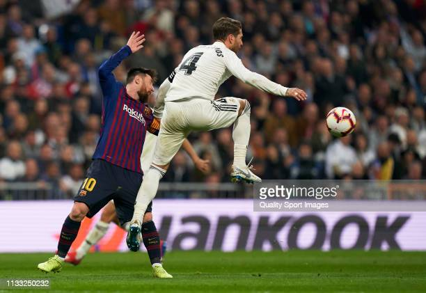 Lionel Messi of Barcelona is tackled by Sergio Ramos of Real Madrid during the La Liga match between Real Madrid CF and FC Barcelona at Estadio...