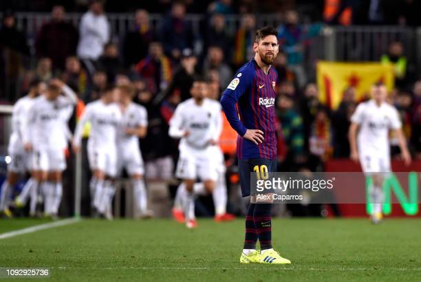 Lionel Messi of Barcelona looks dejected after Daniel Parejo of Valencia scored their second goal during the La Liga match between FC Barcelona and...