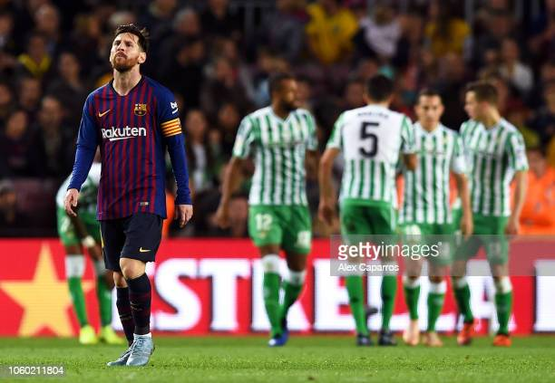 Lionel Messi of Barcelona looks dejected as players of Real Betis celebrate a goal during the La Liga match between FC Barcelona and Real Betis...