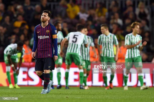 Lionel Messi of Barcelona looks dejected as the Real Betis players celebrate their sides fourth goal during the La Liga match between FC Barcelona...