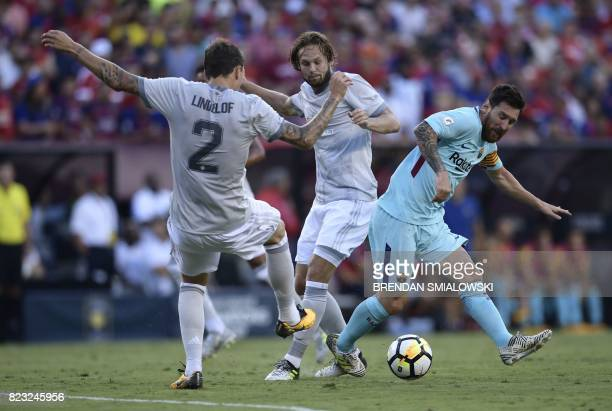 Lionel Messi of Barcelona moves the ball past Victor Lindelöf and Daley Blind of Manchester United during their International Champions Cup football...