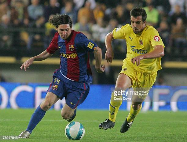Lionel Messi of Barcelona powers past Jose Enrique of Villarreal during the Primera Liga match between Villarreal and Barcelona at the Madrigal...