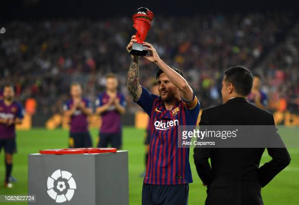 Lionel Messi of Barcelona raises a trophy after being named Player of the Month for September in La Liga during the La Liga match between FC...