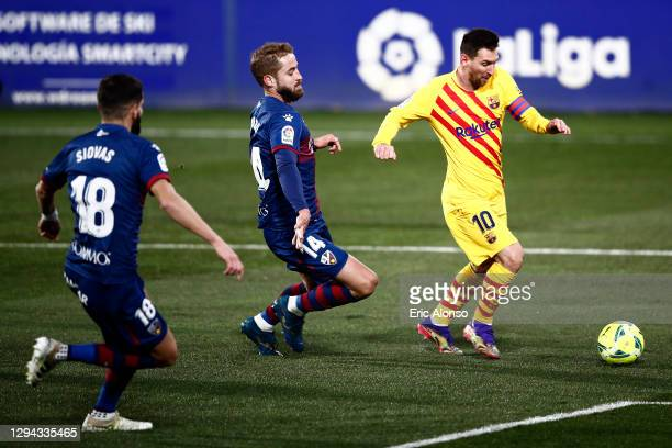 Lionel Messi of Barcelona runs with the ball under pressure from Jorge Pulido and Dimitris Siovas of SD Huesca during the La Liga Santander match...
