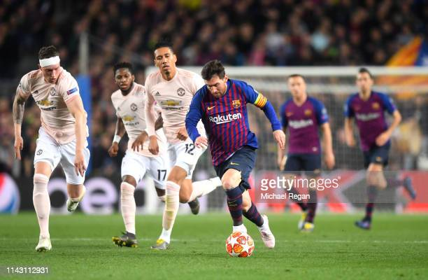 Lionel Messi of Barcelona runs with the ball while under pressure from Phil Jones of Manchester United during the UEFA Champions League Quarter Final...