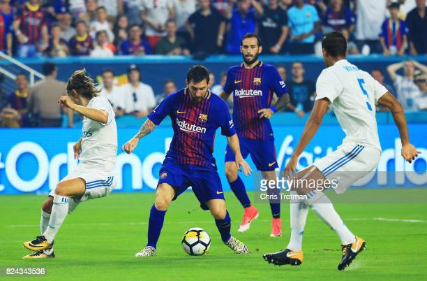 Lionel Messi of Barcelona scores against the defense of Raphael Varane and Luka Modric of Real Madrid in the first half during their International...