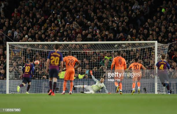 Lionel Messi of Barcelona scores his team's first goal from a penalty past Anthony Lopes of Olympique Lyonnais during the UEFA Champions League Round...