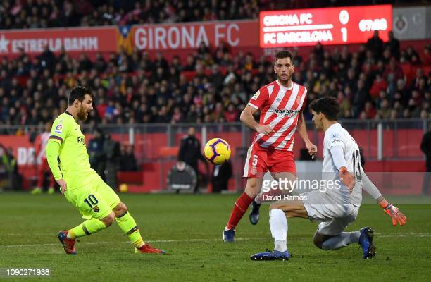 Lionel Messi of Barcelona scores his team's second goal past Yassine Bounou of Girona as Pedro Alcala of Girona reacts during the La Liga match...