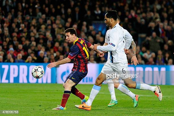 Lionel Messi of Barcelona scores the opening goal as Joleon Lescott of Manchester City closes in during the UEFA Champions League Round of 16, second...