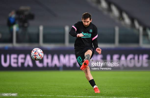 Lionel Messi of Barcelona shoots during the warm up ahead of the UEFA Champions League Group G stage match between Juventus and FC Barcelona at...