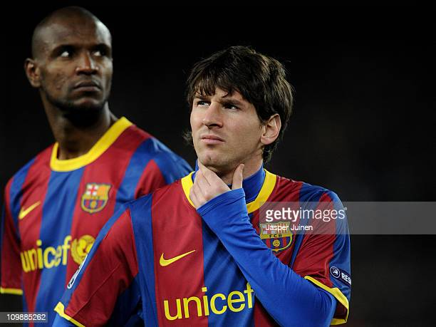 Lionel Messi of Barcelona stands besides his teammate Eric Abidal prior to the start of the UEFA Champions League round of 16 second leg match...