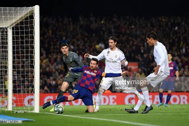 Lionel Messi of Barcelona stretches to keep the ball in play under pressure from Sergio Ramos of Real Madrid during the Liga match between FC...