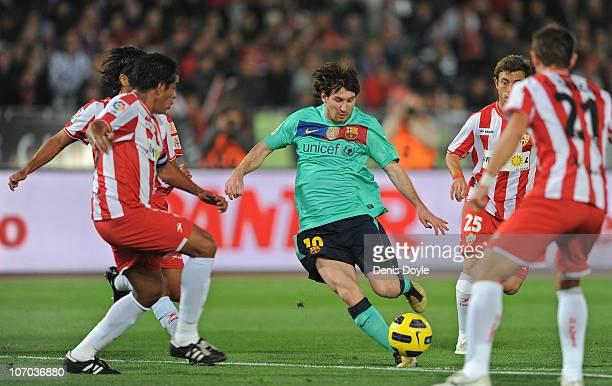 Lionel Messi of Barcelona takes on the UD Almeria defense during the La Liga match between UD Almeria and Barcelona at Estadio del Mediterraneo on...