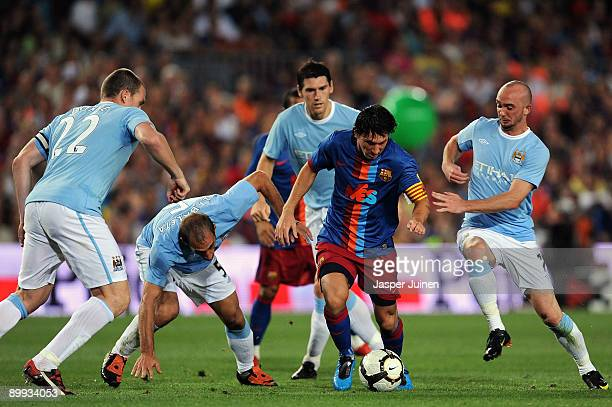 Lionel Messi of Barcelona tests the defence of Manchester City Richard Dunne Pablo Zabaleta Gareth Barry and Stephen Ireland during the Joan Gamper...