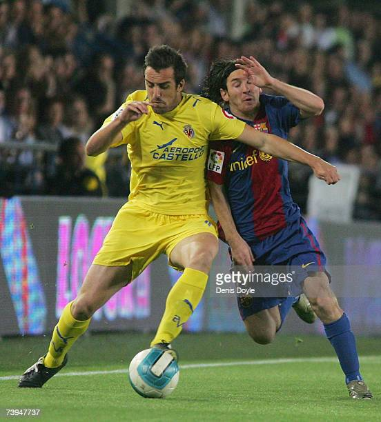 Lionel Messi of Barcelona vies for the ball against Jose Enrique of Villarreal during the Primera Liga match between Villarreal and Barcelona at the...