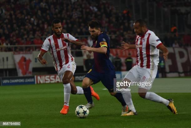 Lionel Messi of Barcelona vies for the ball with Olympiakos' Belgian midfielder Vadis Odjida and Olympiakos' FrenchTogolese midfielder Alaixys Romao...