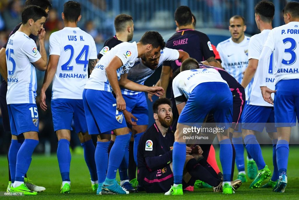 Lionel Messi of FC Barcelona argues with Malaga players after being brought down during the La Liga match between Malaga CF and FC Barcelona at La Rosaleda stadium on April 8, 2017 in Malaga, Spain.