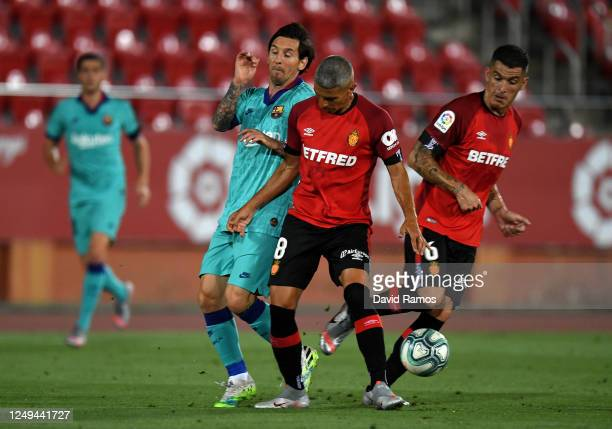 Lionel Messi of FC Barcelona battles for possession with Salva Sevilla of RCD Mallorca during the La Liga match between RCD Mallorca and FC Barcelona...