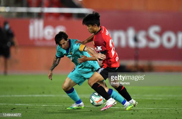 Lionel Messi of FC Barcelona battles for possession with Takefusa Kubo of RCD Mallorca during the La Liga match between RCD Mallorca and FC Barcelona...