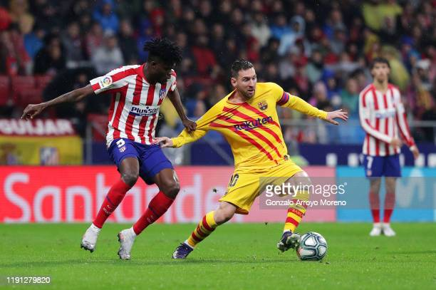 Lionel Messi of FC Barcelona battles with Thomas Partey of Atletico Madrid during the Liga match between Club Atletico de Madrid and FC Barcelona at...