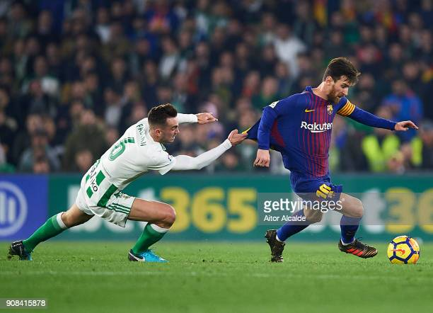 Lionel Messi of FC Barcelona being followed by Fabian Ruiz of Real Betis Balompie during the La Liga match between Real Betis and Barcelona at...
