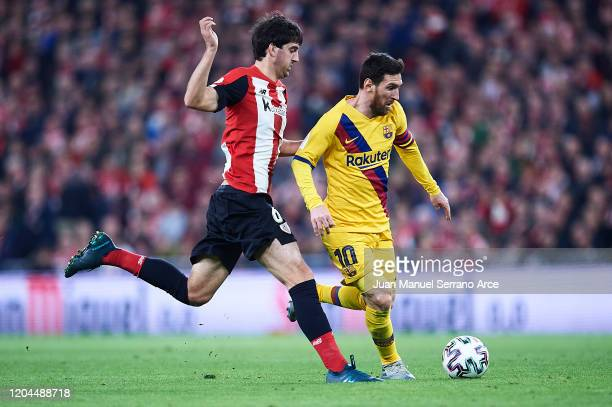 Lionel Messi of FC Barcelona being followed by Mikel San Jose of Athletic Club during the Copa del Rey quarter final match between Athletic Bilbao...